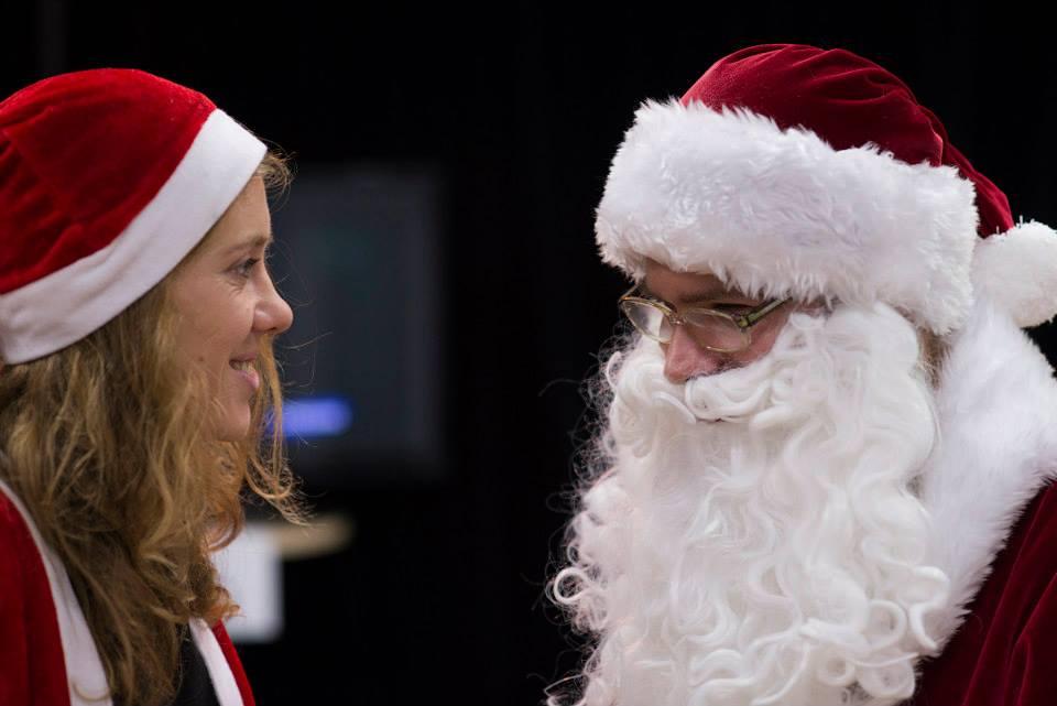 Zdjęcie przdstawia Panią Patrycje Bartoszak, wraz z jednym z aktorów. Oboje ubrani są w stroje świętego mikołaja, czerwone czapki i wąsy. Zdjęcie pochodzi z obchodów świąt bożego narodzenia. Oboje się uśmiechają.