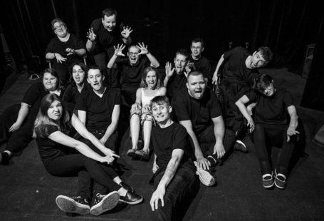 Biało czarne zdjęcie przedstawia aktorów teatru, siedzący na posadzce teatru, uśmiechnięci, wszyscy w czarnych strojach.