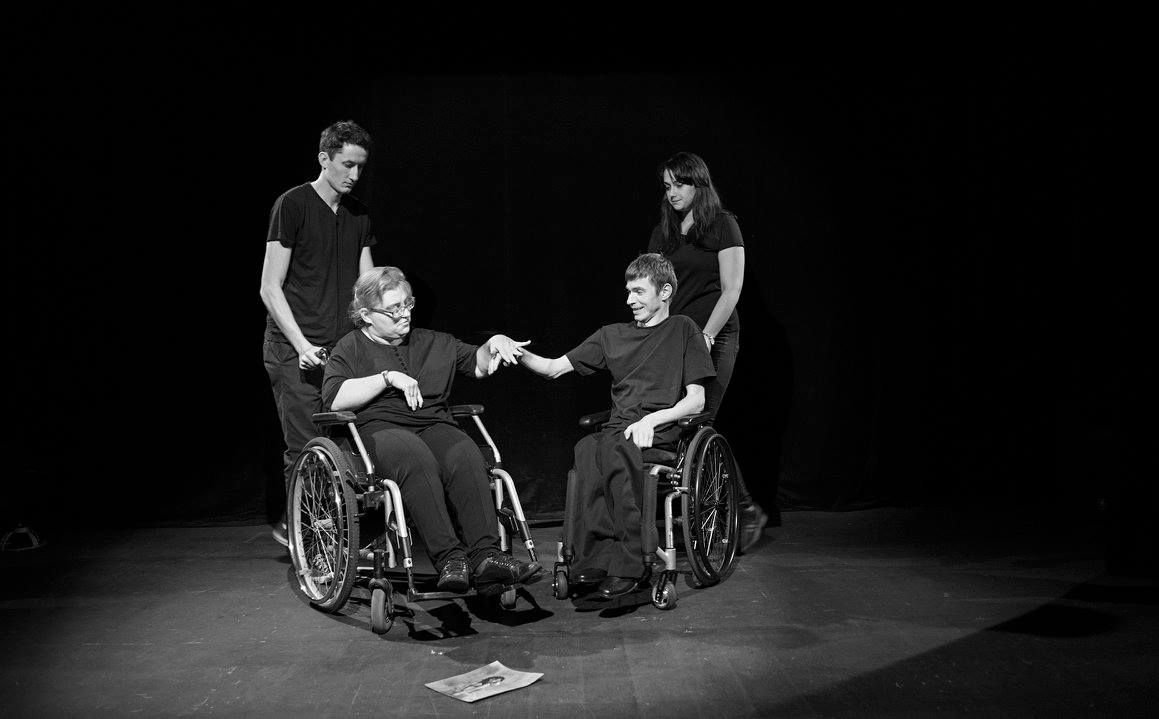 Zdjęcie przedstawia cztery postaci, w tym dwóch aktorów na wózkach. Zdjęcie jest biało czarne, stroje aktorów czarne. Aktorzy wykonują gesty rękami.