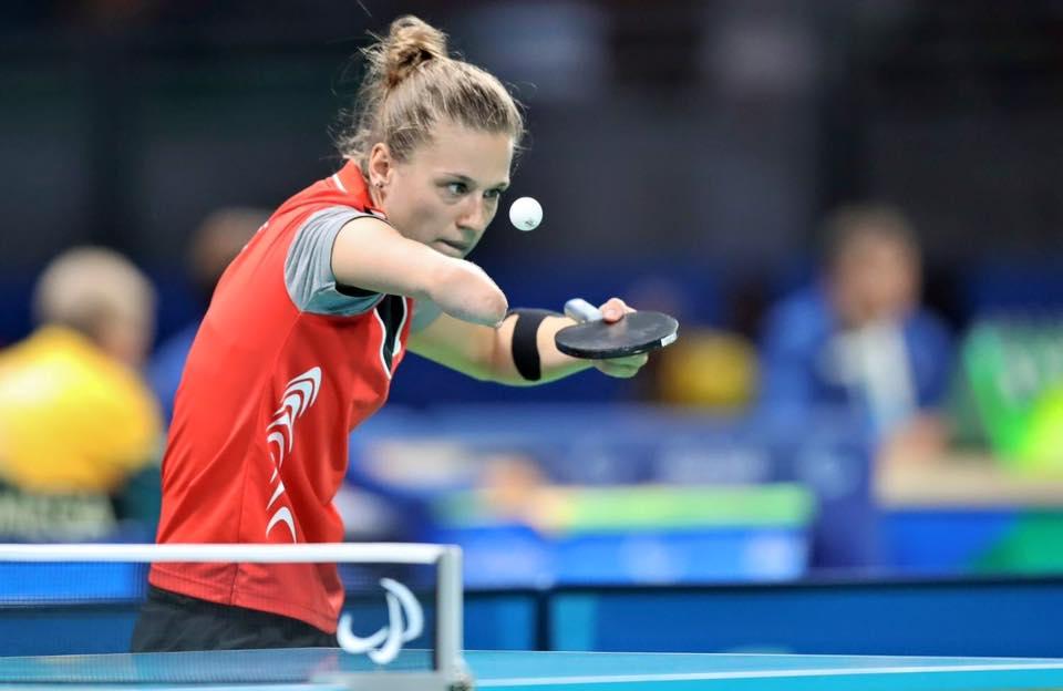 Zdjęcie przedstawia Natalię Partykę na meczu, w momencie kiedy podrzuca piłeczkę, żeby zaraz zaserwować. Patrzy skupieniu na piłeczkę.