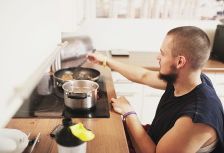 Zdjęcie przedstawia poodpiecznego Akademii, chłopaka wózku, który gotuje obiad. Widzimi jego głowę oraz tułów, jedną rękę opiera na blacie obok kuchenki, drugą miesza danie na pateli, patrząc na nią.