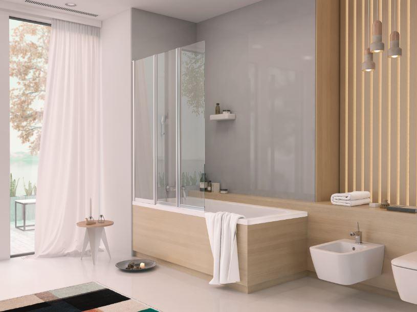 Zdjęcie przedstawa łazienke, w odcieniach beżu i szarości. Na środku znajduje się wanna, obudowana drewnem. Przy oknie powiewają białe, lekkie zasłony.