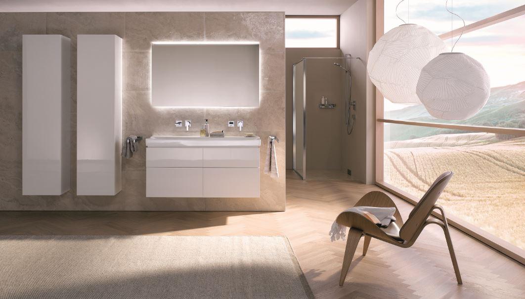 Obrazek przedstawia jasną łazienke, w któej przeważa kolor beżowy. Głównym elementem łazienki jest duże okno, przez które wpada światło słoneczne. Całość jest lekka i eteryczna.