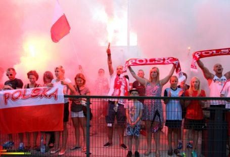 Zdjęcie przedstawia kibiców polskich podczas meczu z Rosją. Wszyscy ubrani w barwy narodowe, weseli i rozentuzjazmowani.