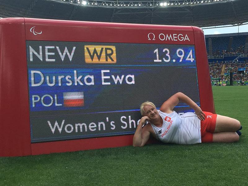 Zdjęcie przedstawia beztroską panią Ewę Durską, leżącą przed olimpijskim telebimem. Pani Ewa jest uśmiechnięta i bardzo dumna z rekordu jaki pobiła. Jej nazwisko, wynik i polska flaga wyświetlone są na telebimie.