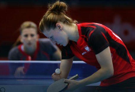 Natalia partyka widziana od lewego profilu, skupiona na serwisie piłki pingpongowej.
