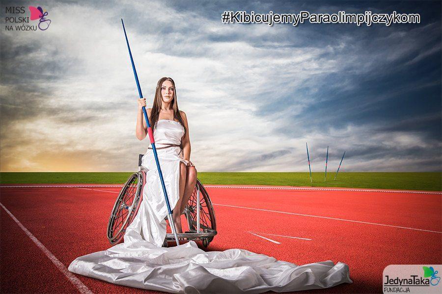 Zdjęcie przedstawia zwyciężczynie konkursu miss na wózku Adę Zawadzińską, w greckim stroju, niczym bogini. Ada trzyma w ręku tyczkę. Scena ma miejsce na czerwonej murawie. Chmury na niebie nadają poważnej, groźnej atmosfery.