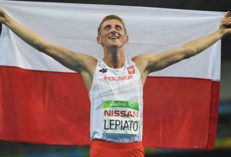 Zdjęcie przedtawia Macieja Lepiato który trzyma flagę Polski na Igrzyskach w Rio. Ma zamknięte oczy i się uśmiecha.