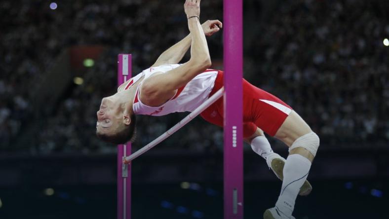 Zdjęcie przedstawia Macieja Lepiato w trakcie skoku wzwyż. Ujęcie wykonane jest gdy zawodnik znajduje się nad poprzeczką.