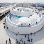 Zdjęcie przedstawia budynek-ślimaka, na który można wjechać rowerem po okrągłej, spiralnej rampie. Budynek jest otwarty, znajdują się na nim miejsca gdzie można usiąść, parasole, basen. Stanowi ptzykład rozwiązania jakie można by zastosować w przyszłości w miastach.