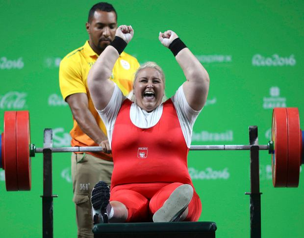 Zdjęcie przedstawia Marzenę Ziębę po podniesieniu ciężaru. Siedzi na ławce, ma podniesione do góry ręce i śmieje się, Za nią na uchwytach stoi sztanga oraz mężczyzna, który asystował przy podnoszeniu.