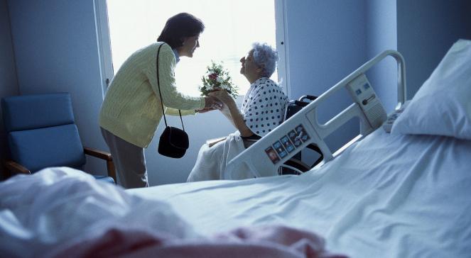 Zdjęcie przedstawia dorosłą kobietę, która daje prezent w postaci kwiatów starszej, schorowanej kobiecie na wózku inwalidzkim. Na pierwszym planie jest łózko szpitalne, na drugim kobiety znajdujące się przy oknie.