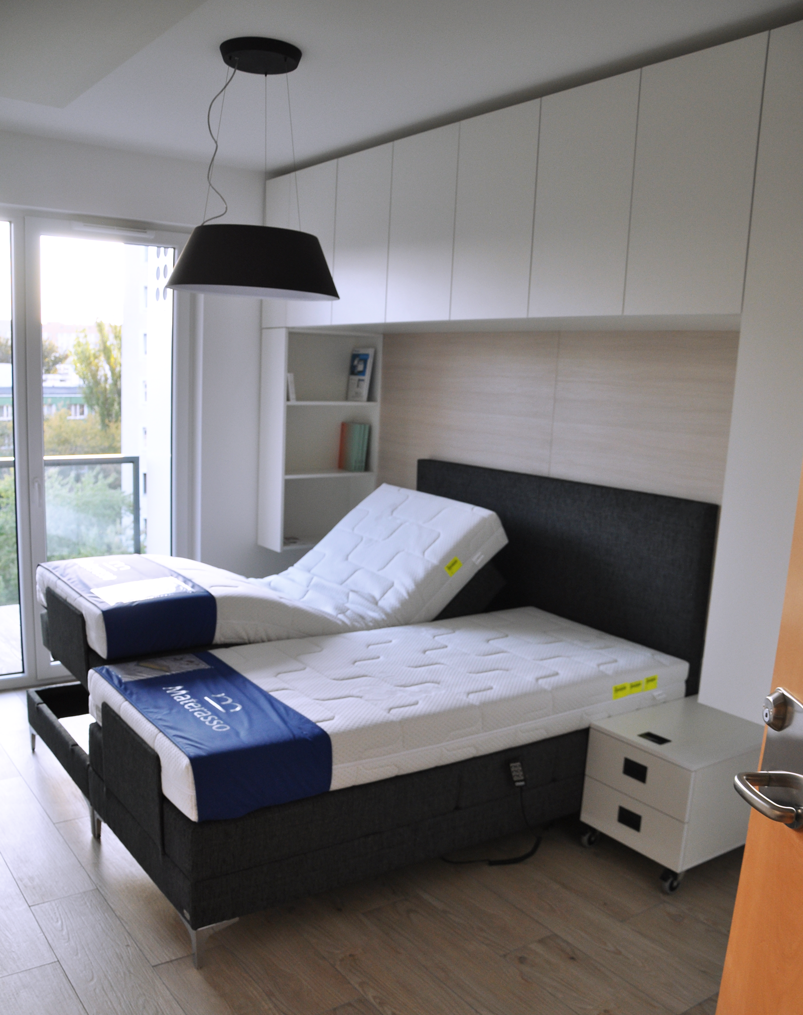 Zdjęcie przedstawia sypialnię w mieszkaniu przystosowanym dla seniora. Znajduje się w niej łóżko z dwoma, podnoszonymi materacami. WIdać wejście na balkon oraz szafki obok łóżka.