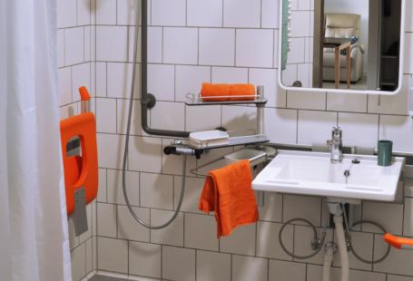 Zdjęcie przedstawia wnętrze łazienki w mieszkaniu zaprojektowanym dla seniora. Po lewej stronie znajduje się prysznic bez progu przy brodziku. Na ścianie na przeciwko drzwi znaduje się umywalka oraz lustro.