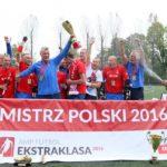Zdjęcie przedstawia zawodników Husarii Kraków cieszących się ze zwycięstwa. W środku trener trzyma puchar podniesionej wysoko ręce. Wokół niego są zawodnicy, również bardzo cieszą się z wygranej, podnoszą kule, ręce, śmieją się. Z prawej strony drugi trener oblewa ich szampanem.