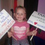 """Na zdjęciu widnieje mała dziewczynka na wózku inwalidzkim, trzymająca dwie tabliczki z hasłami """"TAK dla NUSINERSENU w Polsce"""", oraz """"Pani Premier, chcę ŻYĆ na własnych nogach! - Maja, lat 3."""