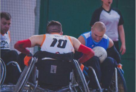 Zdjęcie przedstawia trzech zawodników na meczu. Jednego widzimy tyłem, próbuje odebrać piłkę innemu. W tle widać sędziną.
