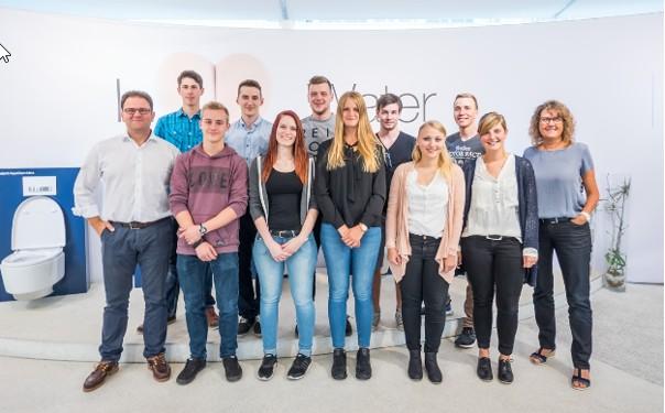 Zdjęcie przedstawia wolontariuszy Geberitu, którzy przez 2 tygodnie będą remontować łazienki w szkole w Warszawie. Na zdjęciu stoi w dwóch rzędach 12 osób.