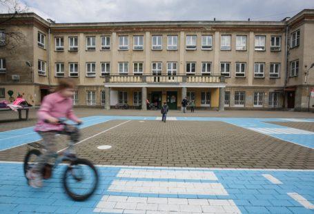 Zdjęcie przedstawia fasadę szkoły na Woli. Na pierwszym planie widać dziewczynkę, która jedzie na rowerze.