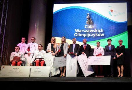 Na zdjęciu znajdują się wszyscy nagrodzeni sportowcy, trenerzy i działacze, stojący na scenie, na Gali Warszawskich Olimpijczyków. Każdy z nich trzyma Dyplom i pozuje do wspólnej fotografii.