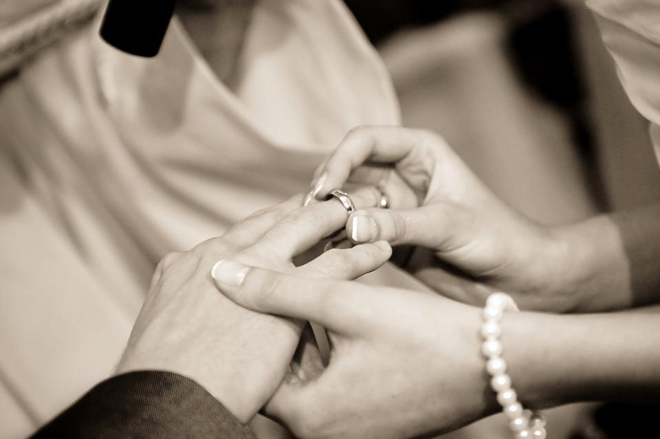 Zdjęcie przedstawia kadr z ceremonii zaslibin, dwie dłonie kobiety i mężczyzny. Kobieta jest w trakcie zakładania obraczki na palec przyszłego męża. Zdjęcie jest czarno-białe.