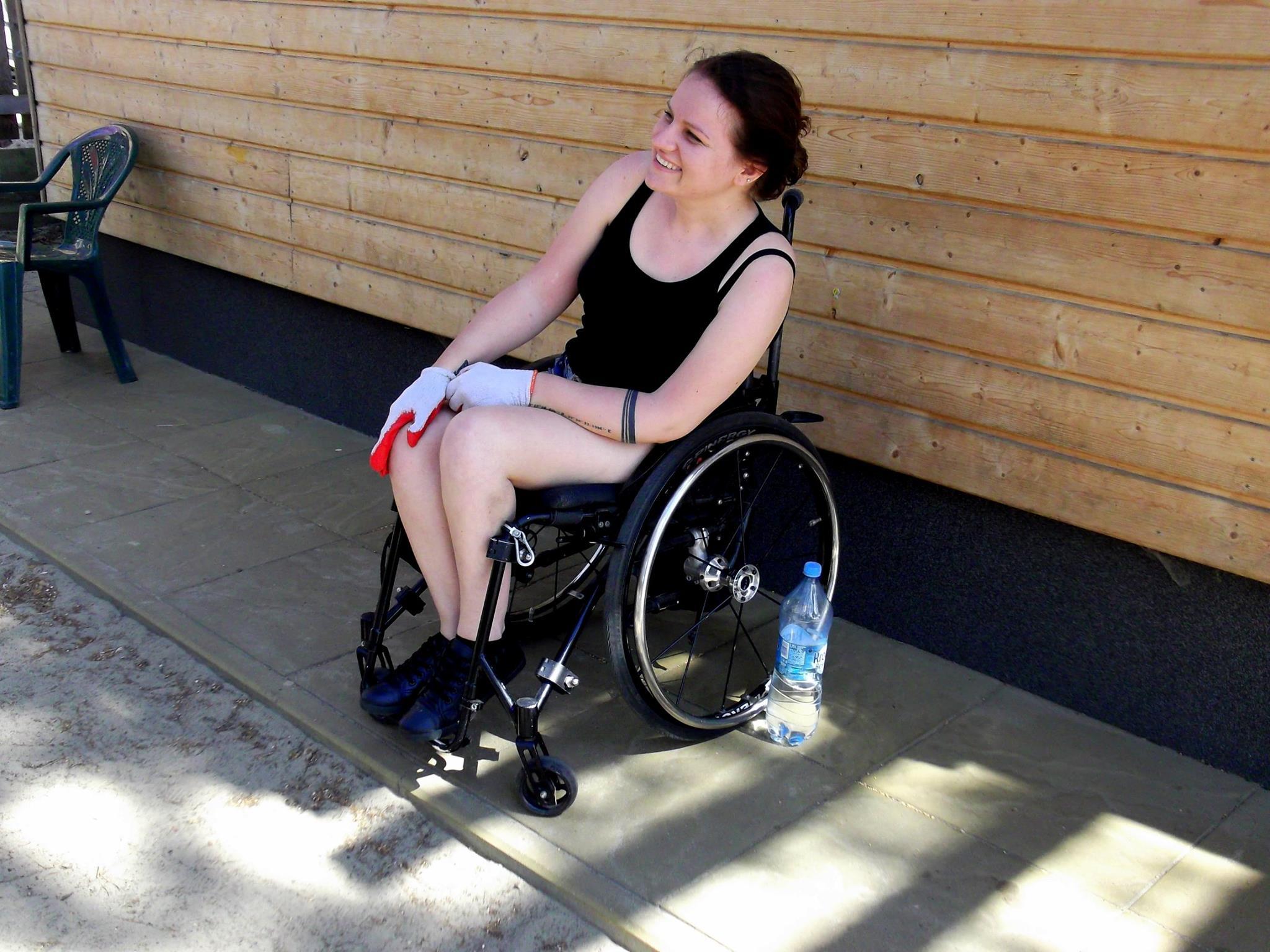 Uśmiechnięta Katarzyna Bierzanowska na tle drewnianej ściany domu. Ma ubrane rękawice ogrodowe, obik niej stoi butelka wody mineralnej.