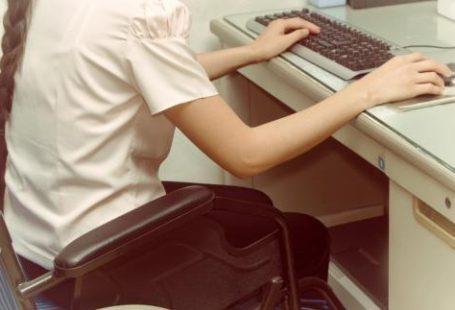 Zdjęcie przedstawia niepełnosprawna dziewczynę siedzaca na wózku inwalidzkim przy biurku przed komputerem stacjonarnym. Jeda ręke trzyma na klawiaturze, druga na myszce.