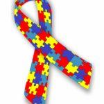 Na obrazku znajduje sie wstążka w kolorowe puzzle (żółte, czerwone, jasny i ciemny niebieski), jest to znak solidarności z osobami chorymi na autyzm. Wzór puzzli symbolizuje złożoność spektrum autystycznego.