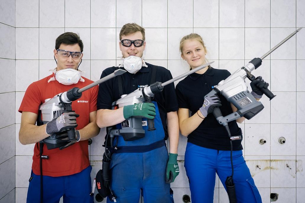 Na zdjęciu widać trzech młodych wolontariuszy (dwóch mężczyzn i kobieta) w ubraniach i okularach ochronnych, pozujących dla żartu z młotami udarowymi, w tle ściana łazienki w płytkach.