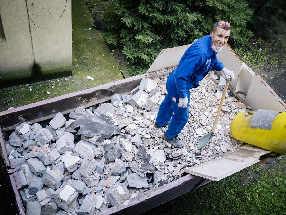 Na zdjęciu znajduje się wolontariusz Geberitu w trakcie remontu, usmiechnietego, stojącego w kontenerze z gruzem