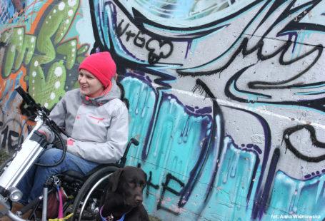 Na zdjeciu znajduje sie uśmiechnięta Katarzyna Bierzanowska, siedząca na wózku inwalidzkim, na tle ściany z graffiti. obok niej siedzi czarny pies rasy labrador. Ubrana w wełnianą różową czapkę oraz, czarne rękawiczki oraz szara kurtkę.
