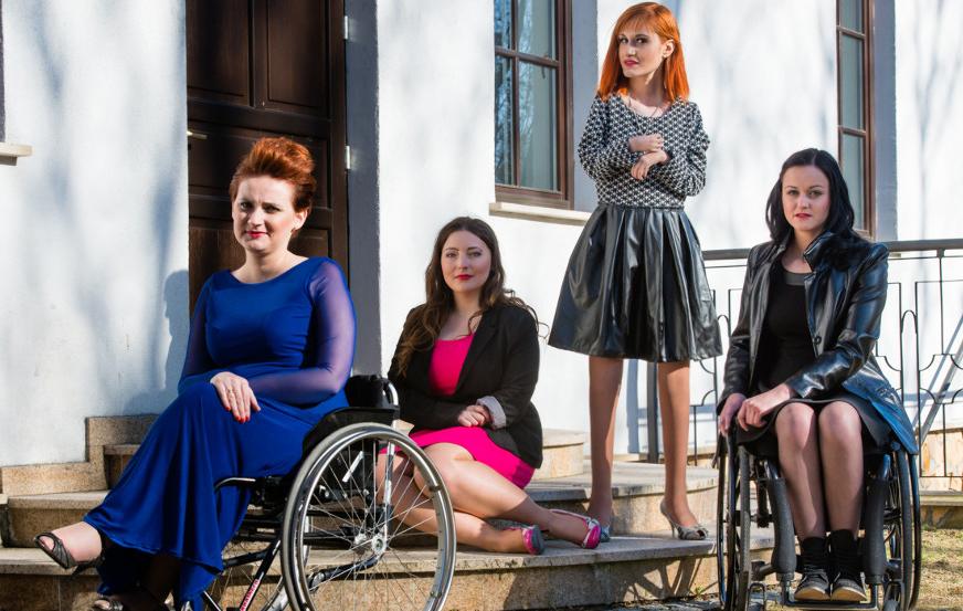 Na zdjęciu znajduja sie cztery piękne kobiety - Modelki z Equal Models Agency, Monika Goliaszewska, Martyna Łysakiewicz, Sylwia Gajewska i Natalia Grynkiewicz. Dwie z nich wcieliły się w rolę hostess z niepełnosprawnością prowadząc Galę. Dwie Panie po bokach pozują na wózku inwalidzkim, Pani po srodku siedzzi na schodach, a kolejna stoi obok. Wszystkie sa pięknie ubrane w suknie wieczorowe, maja piekne fryzury i makijaże i wygladaja zjawiskowo.
