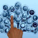 Na obrazku znajduje się dłoń z wyciagnietym palcem wskazującym, dotykającym ikonkę - aplikację internetową. Wszystkie aplikacje rozrzucone są w taki sposób względem siebie, jakby były na gałęziach drzew. Są niebieskie na błękitnym tle.