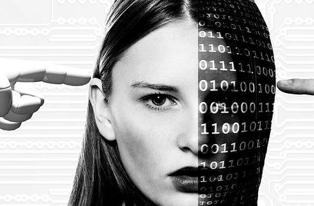 Zdjęcie przedstawia najprawdopodobniej sztuczną inteligencję, nowoczesną technologię, przyszłość. Na obrazku znajduje się kobieta, której połowę twarzy zajmują rzędy cyfr. Z prawej strony strony znajduje sie ludzka dłoń, ułożona w pięść z wysuniętym w stronę głowy kobiety wskazującym palcem. Natomiast ze strony lewej, po drugiej stronie twarzy znajduje się tak samo ułożona dłoń, lecz robota.