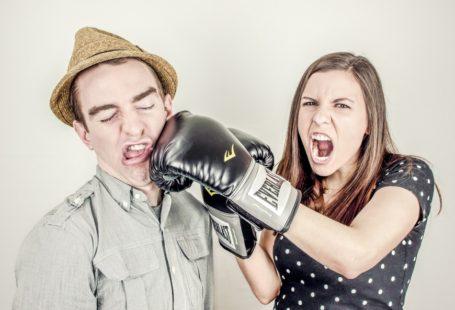 Na zdjęciu znajduje się kobieta i mężczyzna. Kobieta stojąca po prawej stronie ma założone rękawice bokserskie i uderza w twarz mężczyznę po lewej stronie. Po wyrazie twarzy kobiety widać, że jest rozwścieczona i nastawiona na atak. Ma otwarte usta jakby krzyczała. Mężczyzna jest w tej sytuacji ewidentnie ofiarą.