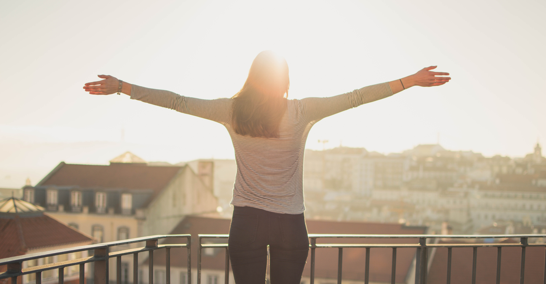 Na zdjęciu znajduje się kobieta, która odwrócona jest tyłem do obiektywu, a przodem do słońca. Stoi na tarasie i unosi w górę ręce.