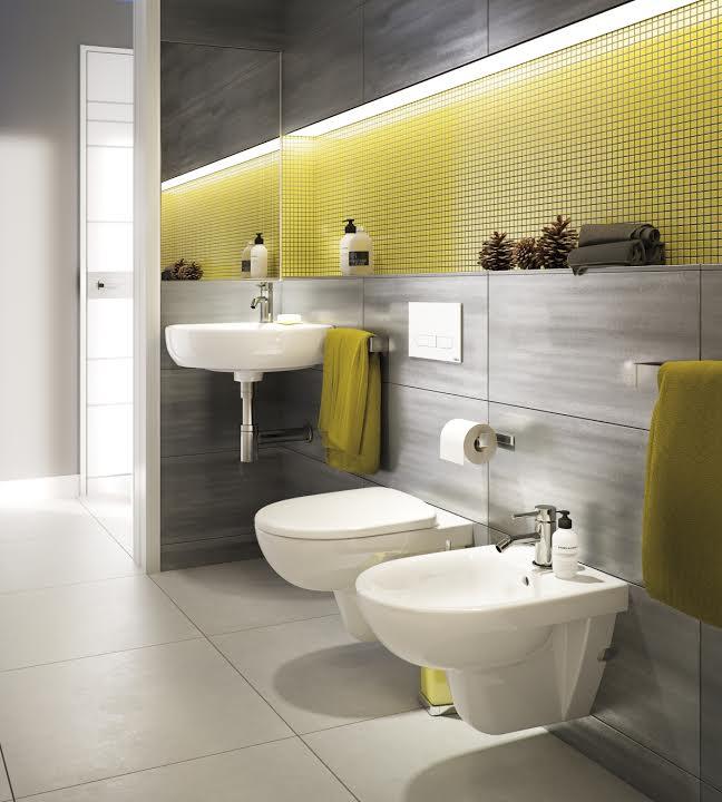 Na zdjęciu znajduje się łazienka w odcieniach szarości i żółci. Od ponad 50 lat KOŁO jest wiodącą na rynku marką wyrobów wyposażenia łazienek w Polsce. Marka jest częścią Grupy Geberit – europejskiego lidera technologii sanitarnych. Oferta obejmuje najwyższej jakości wyroby KOŁO, Keramag i Keramag Design, takie jak: ceramika i meble łazienkowe, wanny i brodziki akrylowe, kabiny prysznicowe oraz systemy instalacyjne.