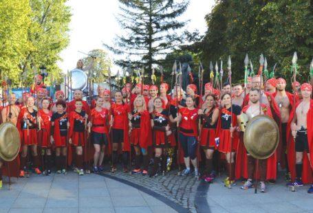 Na zdjęciu znajduje się grupa około sześćdziesięciu osób przebranych za Spartan. Wszyscy mają czerwone peleryny. Kobiety maja czarne bluzki i czerwono czarne spódniczki, a mężczyźni czarne szorty i nagie torsy. Niektórzy trzymają tarcze, a inni włócznie. Wszyscy są uśmiechnięci.