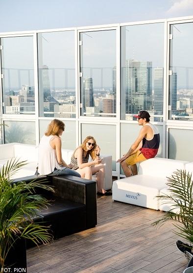 Na zdjęciu widoczni sa rozmawiający ze sobą ludzie, którzy siedzą na kanapach znajdujących sie na dachu jakiegoś wysokiego budynku. Są to trzy osoby, dwie kobiety, jeden mężczyzna. Brzegi dachu otoczone są szkłem, w tle widać panoramę Warszawy.