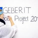 Na zdjęciu znajduje się młoda dziewczyna, wolontariuszka, piszaca na białej ścianie hasło: Geberit Social Projekt 2016
