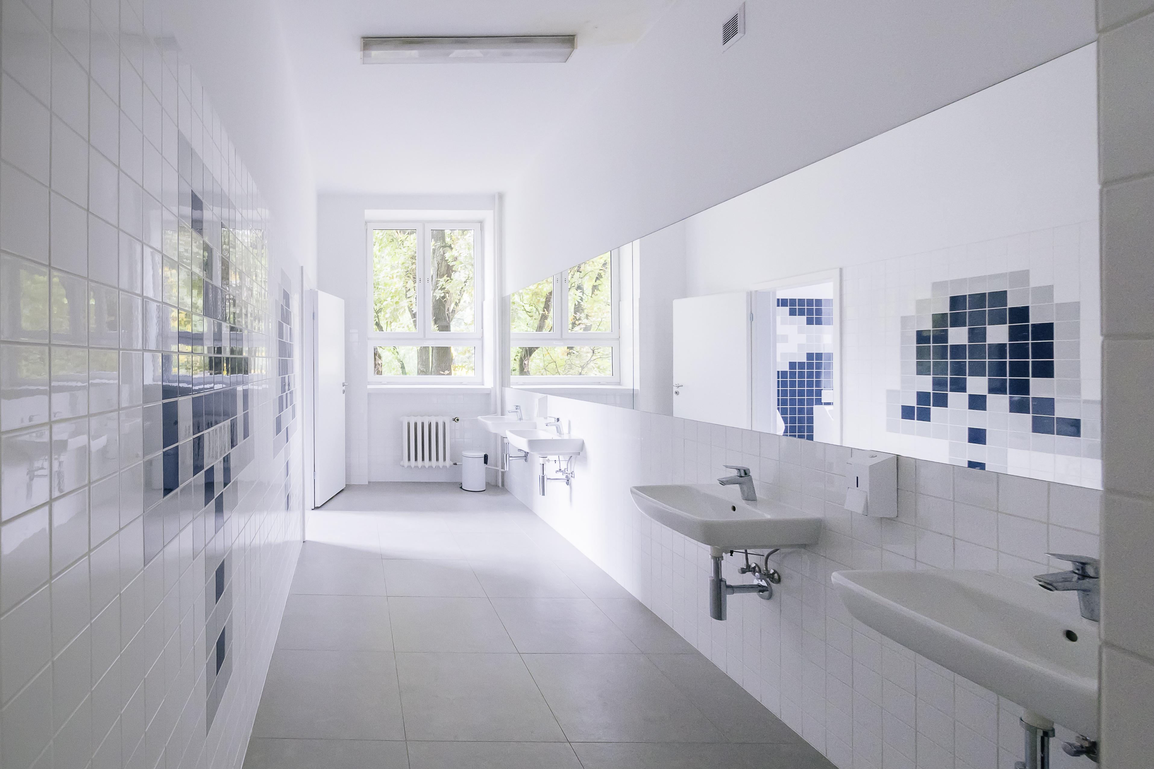 Wyremontowana łazienka w kolorach bieli po prawej stronie na ścianie ułożone są granatowe płytki w kształt pikselowych wzorów, po lewej stronie umywalki z lustrami, naprzeciwko okno. Podłoga w odcieniach szarości.