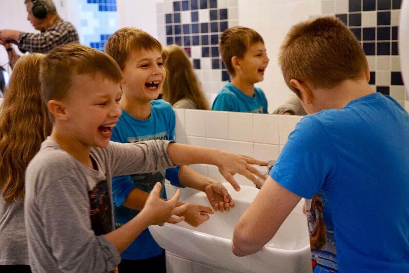 Trzech chłopców myjących ręce w umywalce w nowo wyremontowanej łazience w Szkole Podstawowej na Warszawskiej Woli. Są roześmiani i rozbawieni.