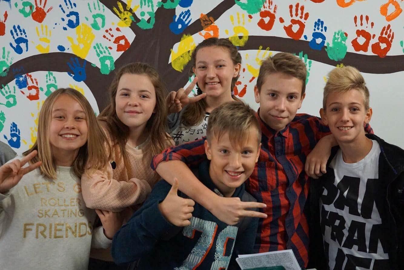 Grupka uśmiechniętych dzieci pozująca na kolorowej ściance w szkole Podstawowej na Warszawskiej Woli. Na ścianie namalowane jest drzewo, a jego korone tworzą poodbijane, kolorowe dłonie dzieci.