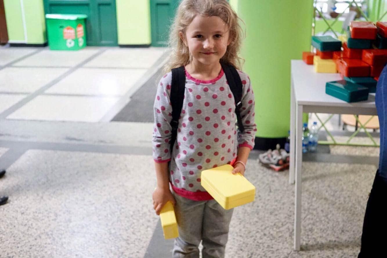Dziewczynka trzymająca dwie gąbki w Szkole podstawowej na Woli. Ma na sobie plecak, ładnie usmiecha sie do zdjęcia.