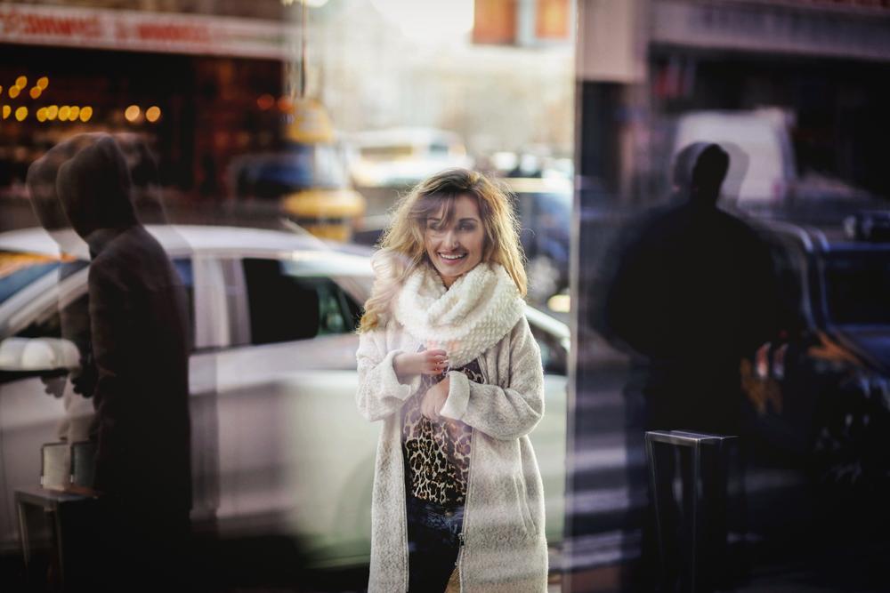 Na zdjęciu widzimy piękną kobietę - Sylwię Gajewską, z nieziemskim uśmiechem, pozującą w scenerii miejskiej. W tle samochody i przechodzący rozmyci ludzie