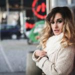 Na zdjęciu znajduje sie piękna kobieta, Sylwia Gajewska, niepełnosprawna modelka. Stoi bokiem do aparatu, opiera się o ścianę, ma lekko rozchylone usta i ujmujący wzrok. W tle widać rozmyte samochody i budynki.