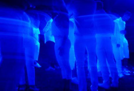 Na zdjeciu widocznych jest pare rozmazanych, tańczących postaci na imprezie. Na bawiących sie ludzi puszczone jest niebieskie światło z reflektora. Zdjęcie jest niewyraźne i ciężko rozróżnić kto dokładnie się na nim znajduje.