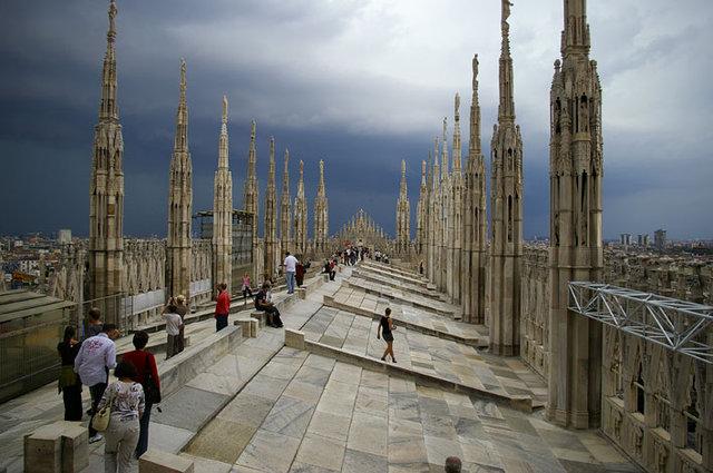 Na zdjęciu widoczny jest dach Katedry Narodzin Św. Marii w Mediolanie, po którym spacerują zwiedzający ludzie.