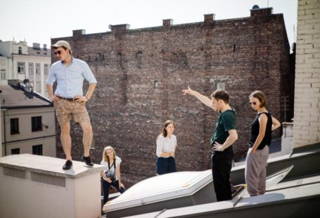 Na zdjęciu widoczni sa młodzi ludzie zwiedzający jeden z Warszawskich dachów.