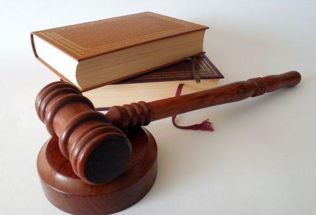 Na zdjęciu na białym tle widoczny jest drewniany młodek sędziowski leżący na okrągłej podkładce z tego samego materiału. Z tyłu za nim leżą dwie książki jedna na drugiej, oprawione w okładkę ze skóry.